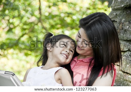 Little girl and mother enjoy tablet PC in park.