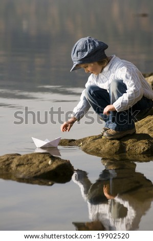 Little girl and paper boat