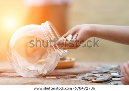 Little girl and pile coin for saving. money saving concept. #678492736