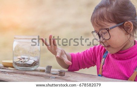Little girl and pile coin for saving. money saving concept. #678582079