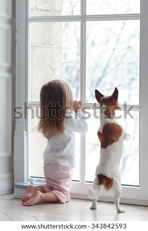Little girl and the dog looking out the window