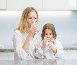 Little girl and woman drink water in the kitchen