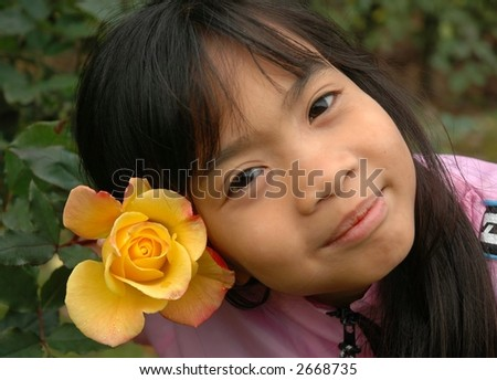 Little girl and yellow rose