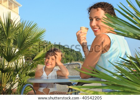 little girl and young woman eat ice-cream near palm trees on resort