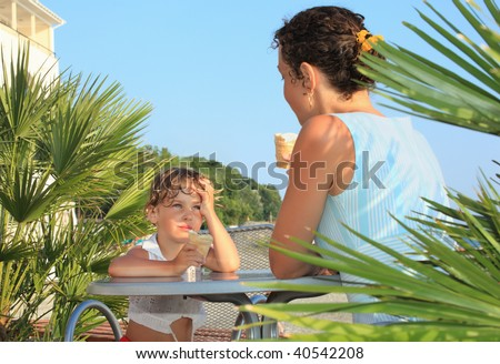 little girl and young woman eat ice-cream near palm trees on resort, Looking against each other