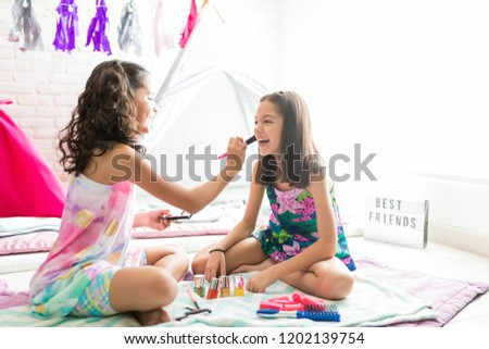 0f46810f33 Little girl applying blush on happy friend s cheek during sleepover party
