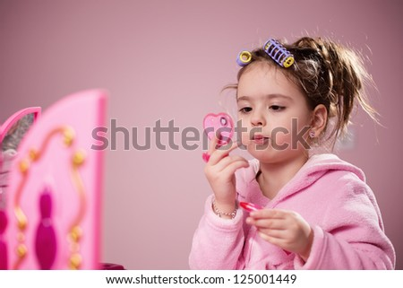 Little girl applying toy lipstick