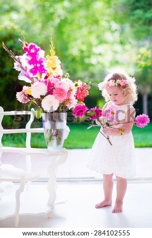 Little girl arranging flowers at home in a vase. Child playing indoors. Kids birthday party. Children giving flower as present. Kid in a living room with big window and door to the garden. Summer fun.