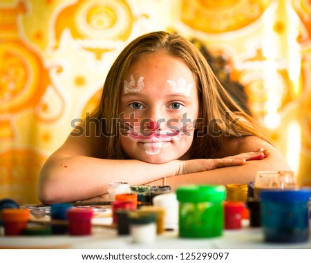 Little girl artist, drawing paint with paint of face.