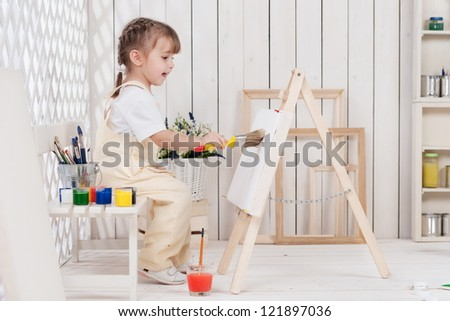 Little girl artist paints in his studio - stock photo