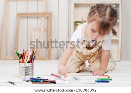 Little girl artist paints in his studio
