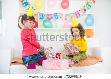 Little girl at a birthday party, furious that are difficult to open birthday gift box. A little blurred motion and shallow doff.