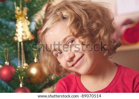 little girl at a Christmas fir-tree.