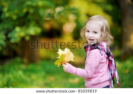 Little girl at autumn park holding yellow leaves