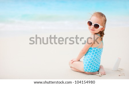 Little girl at beach with sun shaped cream at her back