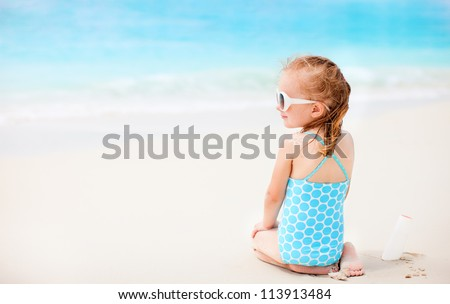 Little girl at beach with sun shaped cream at her shoulder