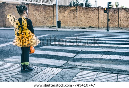 Little girl at stopped at zebra crossing in halloween costumes. She is walking   towards children party site. Badajoz, Spain