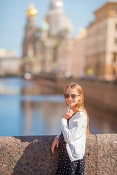 Little girl at the summer waterfront in Saint Petersburg. Girl outdoors with The Church of the Savior on Spilled Blood on background