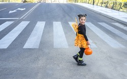 Little girl at zebra crossing in halloween costumes. She is walking towards children party site. Badajoz, Spain