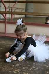 little girl ballerina sits in the studio on the floor and ties up pointe shoes