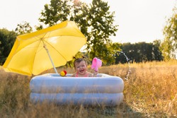 Little girl bathes in an inflatable pool. The village is sunny and warm, the baby has fun and plays in the water.