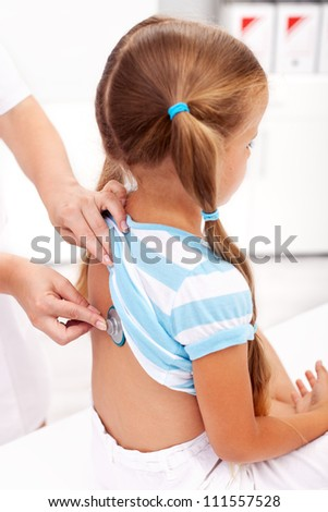 Little girl being checked with a stethoscope at the doctor's - closeup