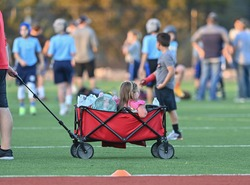 Little girl being pulled in a wagon at a sporting event