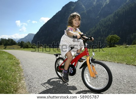 little girl biking in the mountains