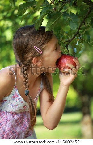 Little girl biting into an apple from an apple tree. Shallow depth of field.