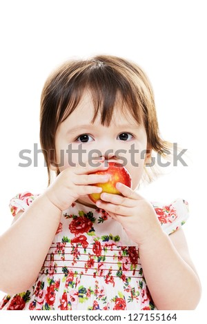 Little girl biting red apple closeup portrait