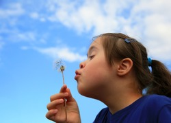 Little girl blowing dandelion on background of the blue sky