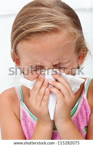 Little girl blowing her nose in a great effort - closeup - stock photo