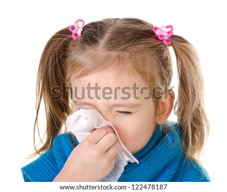 Little girl blowing her nose in a great effort closeup isolated on white