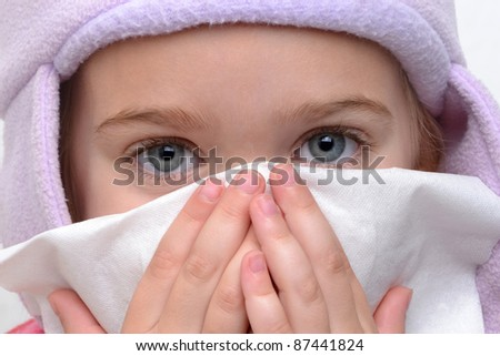 little girl blowing nose with tissue