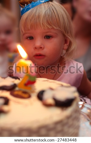 little girl blowing on birthday cake - stock photo