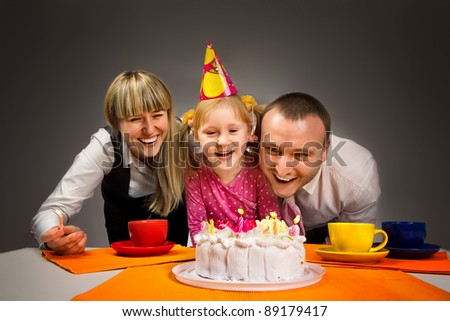 Little girl blowing out candles in her birthday with her happy family