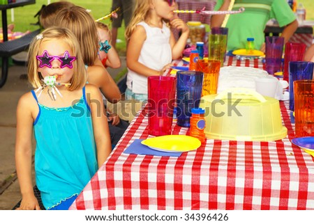 Little girl blowing paper party horn at a birthday party