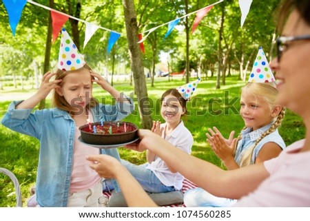 Little girl blowing six candles on birthday cake held by young woman during summer picnic on weekend #1074560285
