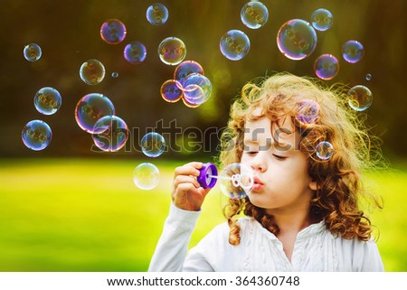 little girl blowing soap bubbles in summer park. Background toning for instagram filter.