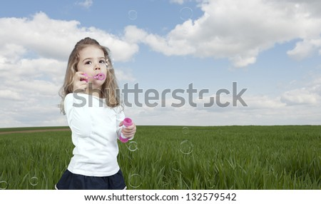 little girl blowing soap bubbles,outdoors in the fields