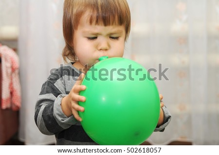 Little girl blowing up a balloon, toddler playing with rubber ball, child training lung making breathe exercise Foto stock ©