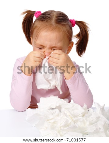 Little girl blows her nose in paper tissue, isolated over white