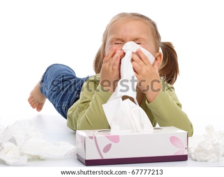 Little girl blows her nose while laying on floor, isolated over white