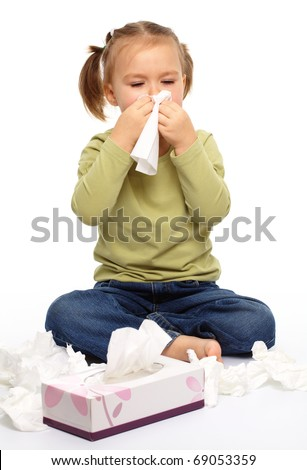 Little girl blows her nose while sitting on floor, isolated over white - stock photo