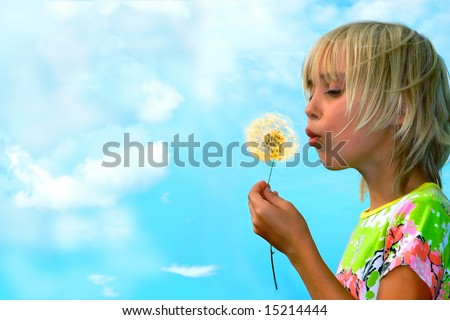 Little girl blows on a seedy pod plant as seeds drift off