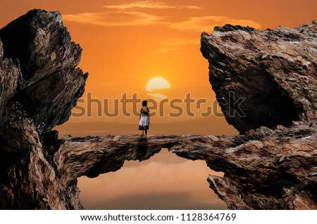 Little girl borrowed to look at the sun is going to land on the cliffs beautiful stone bridge.