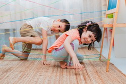 little girl boy brother, siblings, friendschild climbs through a rope web, a game obstacle quest indoors. The concept of active play in the home room, quarantine, self-isolation.