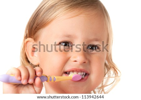 Little girl brushing her teeth, isolated on white background