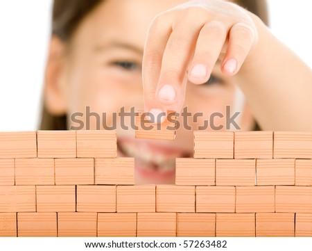 little girl building a wall focused on bricks