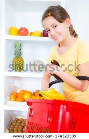 little girl buying fresh fruit at the market